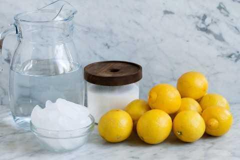 Ingredientes para hacer limonada, incluyendo limones frescos, azúcar, hielo y agua.
