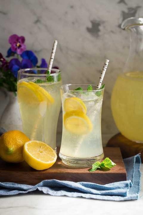 Vidrio de limonada fresca en sol con las flores en el fondo.