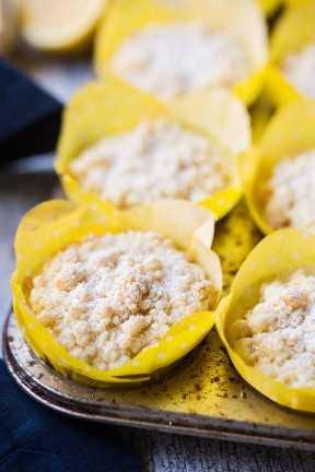 Muffins de limón en una sartén con forros amarillos y azúcar en polvo en la parte superior.