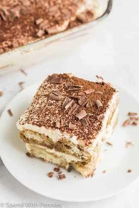 de cerca una rodaja de tiramisú adornada con cacao y chocolate en un plato blanco con una cacerola de tiramisú en el fondo