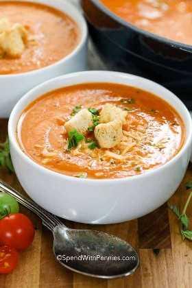Uma tigela branca de sopa de tomate com queijo, croutons e salsa.
