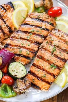 Filetes de salmón a la plancha con verduras asadas y rodajas de limón.