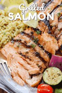 Salmón a la plancha servido con arroz y verduras a la plancha. Adornado con una rodaja de limón y perejil.