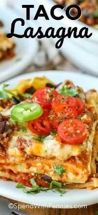 Una rebanada de lasaña inspirada en tacos servida en un plato blanco y adornada con rodajas de tomates cherry