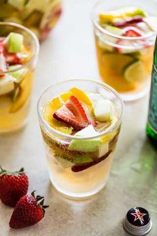 Sangría de vino blanco en un vaso transparente cubierto con fresas en rodajas y fruta de verano.