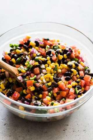 Frijol negro y salsa de maíz en un tazón grande para mezclar vidrio.