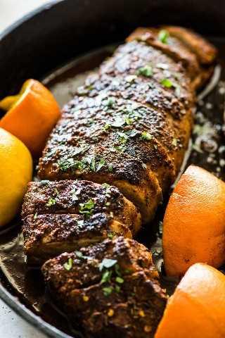 Solomillo de cerdo asado en sartén de hierro fundido negro adornado con cilantro picado.