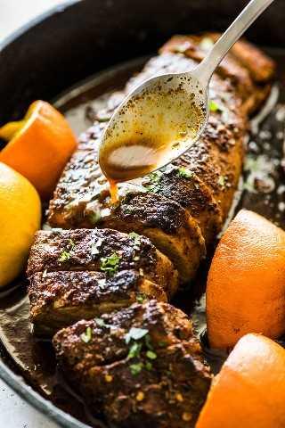 Una cuchara que vierte los jugos del horno de lomo de cerdo de una sartén de hierro fundido negro.
