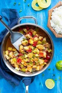 Una sartén grande llena de una receta de cena de pollo de 30 minutos con piña, salsa dulce y pegajosa, junto a un plato de arroz blanco.