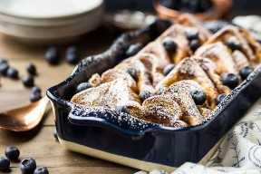 La tostada francesa hecha en casa fresca cocida cuece en un plato azul con los arándanos.