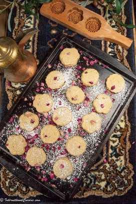 Uma assadeira cheia de belos biscoitos ma'amul cobertos de açúcar em pó e pétalas de rosa.