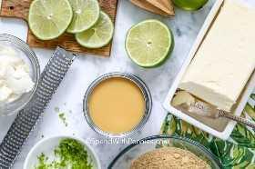Toma superior de los ingredientes clave de la tarta de lima de limas, queso crema, leche condensada, mantequilla y migas de Graham, adornada con ralladura de lima y zester.