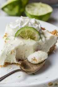 Rebanada de pastel de lima en un plato donde falta un bocado y una cucharada de pastel de lima