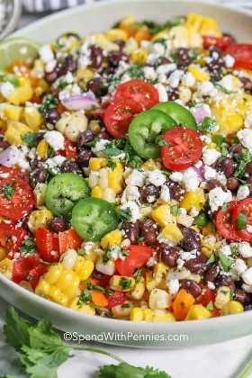 Primer plano de una ensalada de maíz con frijoles negros adornada con jalapeños, tomates cherry y cilantro.
