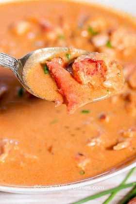Una cucharada de sopa de langosta con trozos de pinza de langosta