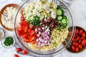Un tazón de ingredientes de ensalada de orzo que incluye tomates, pepinos, aceitunas, cebollas y queso