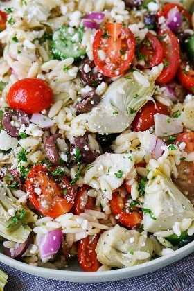 Una foto de una ensalada de orzo lanzada con tomates, alcachofas, pepinos, cebollas y aceitunas