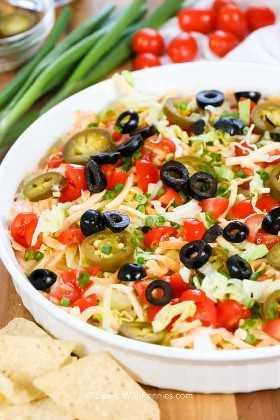 Un rápido baño de tacos de 5 minutos en un tazón cubierto con aderezos de tacos que incluyen tomates, lechuga, jalapeños y aceitunas