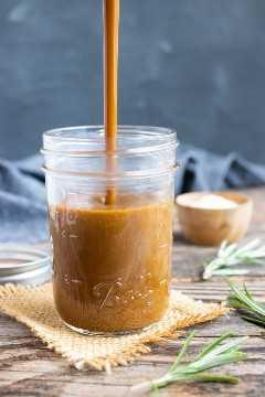 Una receta de vinagreta balsámica fácil que se vierte en un frasco de albañil claro.