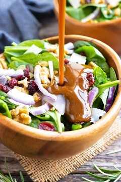 Un aderezo de vinagreta balsámico saludable y fácil que se vierte sobre una ensalada de espinacas con arándanos.