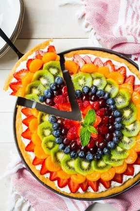 Imagen de arriba de una pizza de frutas del arco iris con una rebanada que se elimina, sobre un fondo blanco con una toalla de cocina roja impresa.