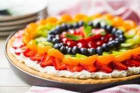 Pizza de frutas hecha de cero con fruta fresca, glaseado de queso crema y una costra de galleta de azúcar.