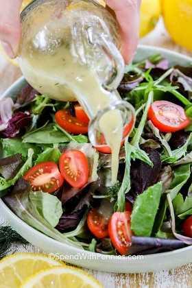 Verter una vinagreta de limón casera sobre una ensalada fresca en un tazón.
