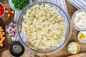 Un tazón de pasta de pajarita con ingredientes de ensalada en tazones a su alrededor.