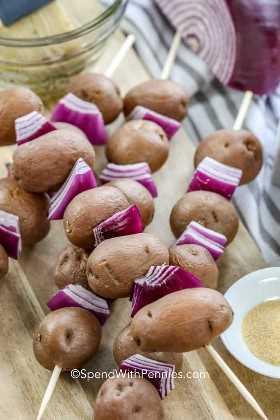 Patatas del bebé y cebollas rojas en los pinchos.