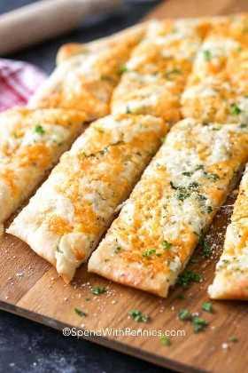 Palitos de pan con queso cortados en palitos en una tabla de cortar, espolvoreados con perejil.