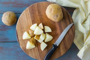 Patatas tajadas en una tabla de cortar de madera.
