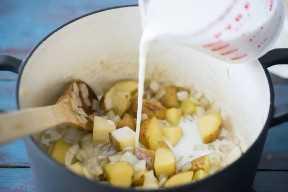 Agregando leche a las papas y cebollas para hacer la sopa.