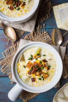 Vista de arriba de dos crocks de sopa de la sopa de pescado, en un fondo azul con una servilleta impresa amarillo.