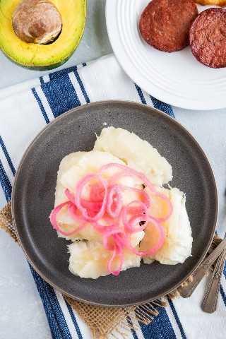 Yuca hervida servida en un plato y coronada con cebollas.