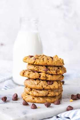 Biscoitos de chocolate com manteiga de amendoim em uma pilha com um copo de leite atrás deles.