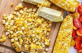 Maíz a la parrilla cortado de la mazorca en una tabla de cortar para hacer ensalada de maíz