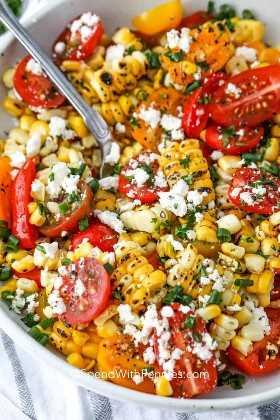 Ciérrese para arriba de un cuenco de ensalada de maíz asada a la parrilla con una cuchara en ella.