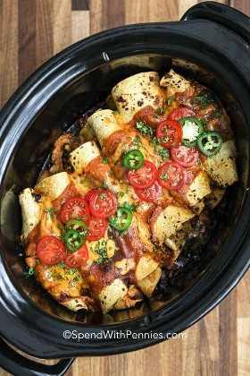Enchiladas de pollo terminadas en capas en una olla de barro, adornada con tomates, jalapeños y cilantro.