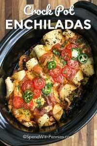 Enchiladas apiladas en una olla de cocción lenta y adornadas con tomates y jalapeños.