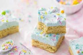 Las barras de galleta de azúcar helada en colores pastel con chispas y una servilleta rosa.