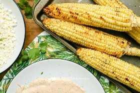 Queso Cotija, mayonesa picante y salsa de crema agria, y maíz asado en una tabla para cortar.