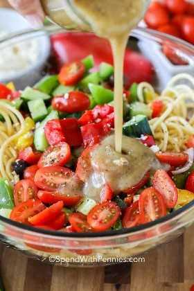 Ensalada de espaguetis en un recipiente con tomates, pepinos y aceitunas con aderezo griego que se vierte sobre.