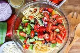 Imagen de arriba de todos los ingredientes de la ensalada de espagueti en un tazón antes de mezclar.