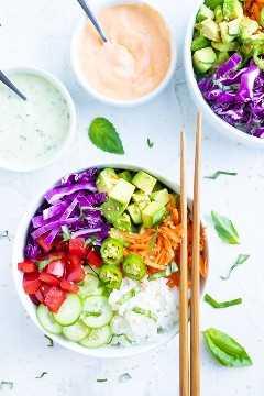 Dos tazones de sushi veganos con dos tazones pequeños de mayonesa de sriracha y salsa de wasabi cilantro.
