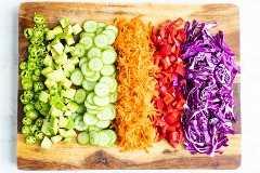 Una tabla para cortar con jalapeño picado, repollo morado, pimiento rojo, zanahorias ralladas, pepino y aguacate para una receta de tazón de sushi vegano.
