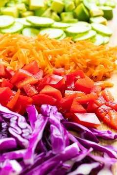 Repollo morado, pimiento rojo, zanahorias ralladas, pepino y aguacate en una tabla para cortar.