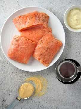 filete de salmón crudo en un plato blanco con polvo de tamarindo y mayonesa en el lado