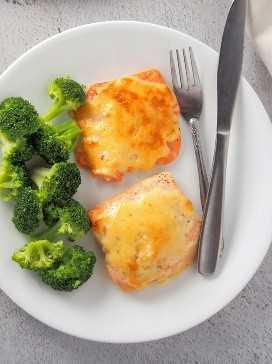 Vista superior de salmón al horno con aderezo de tamarindo mayonesa en un plato blanco con florecillas de brócoli al vapor