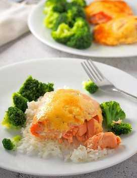Salmón al horno con aderezo de mayonesa sobre el arroz al vapor con brócoli al vapor en el costado