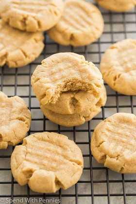 Galletas de mantequilla de maní apiladas en una rejilla de refrigeración con un bocado de una galleta